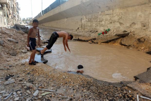 Fëmijët sirianë bëjnë not në gropa të krijuara nga raketat